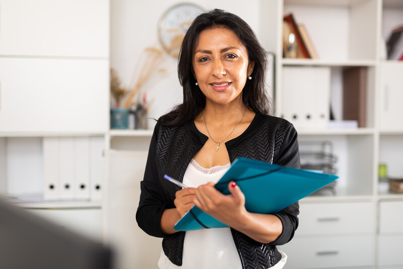 Confident business woman writing tasks in office